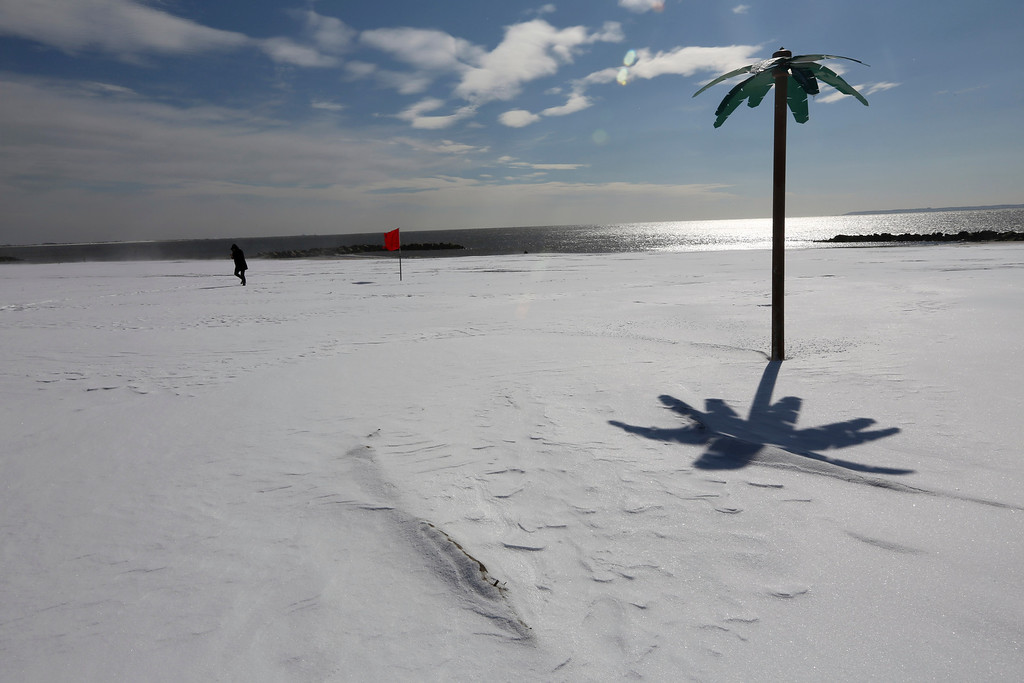 . A man hunches over to protect himself from the wind and blowing snow while walking on the beach at New York\'s Coney Island, Saturday, Feb. 9, 2013. A behemoth storm packing hurricane-force wind gusts and blizzard conditions swept through the Northeast overnight. (AP Photo/Mary Altaffer)