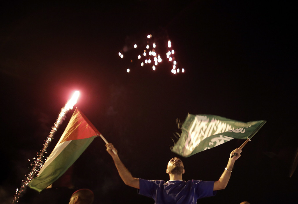 ". A Palestinian waves a national and a Hamas flag as fireworks light up the sky on August 26, 2014 in East Jerusalem as Palestinians celebrate in the streets the long-term truce agreed between Israel and the Palestinians. Israel has agreed to observe an ""unlimited\"" ceasefire in the Gaza Strip, a senior official told AFP, shortly after the deal was announced by the Palestinians AHMAD GHARABLI/AFP/Getty Images"