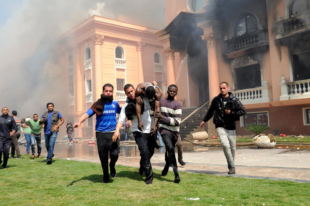 . An injured security official is carried from a police officers club in the upscale neighborhood of Zamalek, after protesters set fires following a court verdict in Cairo, Egypt, Saturday, March 9, 2013.(AP Photo/Mohammed Asad )