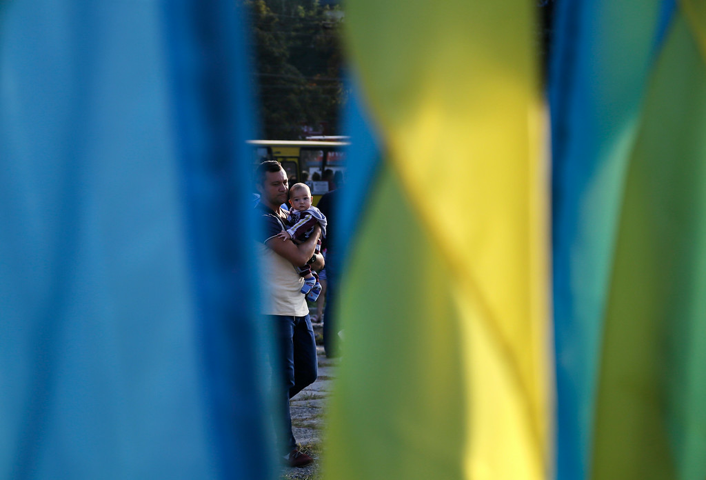 """. A man with his baby is seen between Ukrainian flags prior to an anti-war meeting in the town of Mariupol, eastern Ukraine, Thursday, Aug. 28, 2014. Ukraine\'s president Petro Poroshenko called an emergency meeting of the nation\'s security council and canceled a foreign trip Thursday, declaring that \""""Russian forces have entered Ukraine,\"""" as concerns grew about the opening of a new front in the conflict. (AP Photo/Sergei Grits)"""