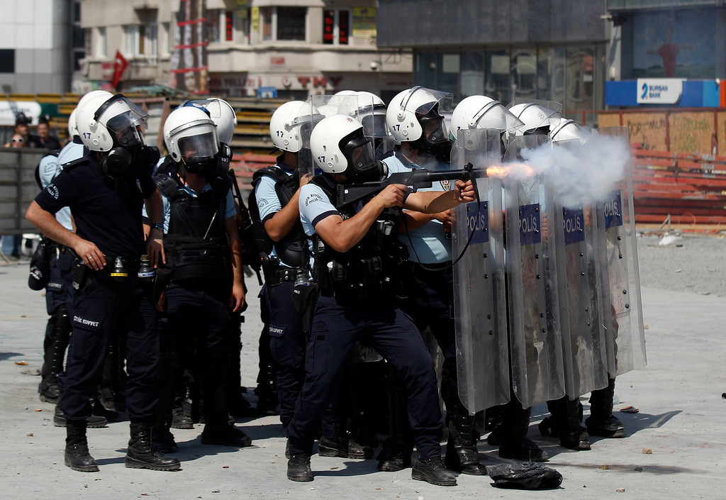 . A riot policeman launches a tear gas canister during clashes in Taksim square in Istanbul, Tuesday, June 11, 2013.  (AP Photo/Kostas Tsironis)