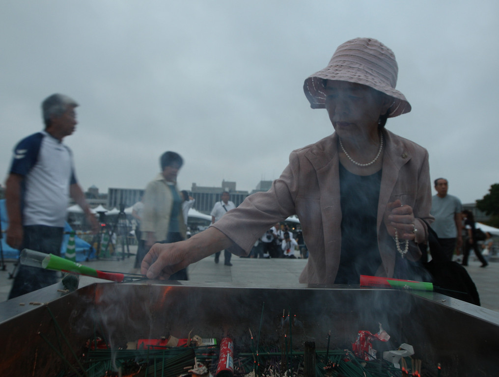 . A woman burns incenses and pray in front of a monument for atomic bomb victims at the Hiroshima Peace Memorial Park on the day of the 68th anniversary of the atomic bombing of Hiroshima on August 6, 2013 in Hiroshima, Japan.  (Photo by Buddhika Weerasinghe/Getty Images)