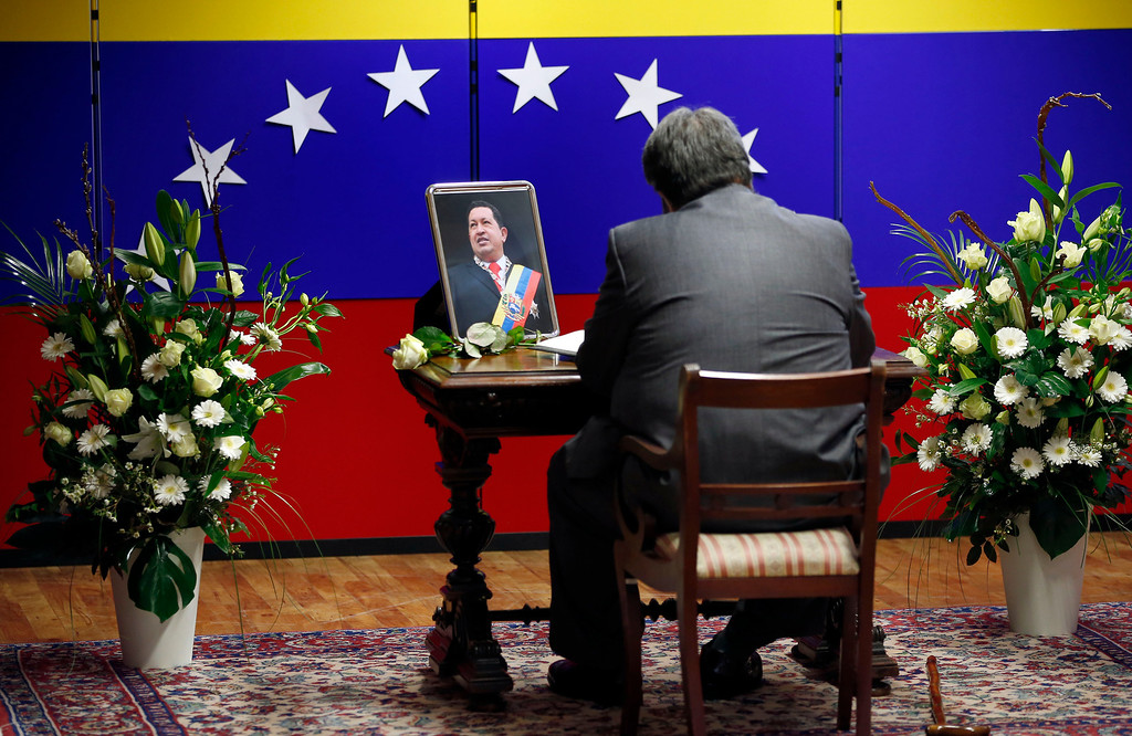 . A man writes a note in a book of condolence at the embassy of Venezuela in Berlin, Germany, Wednesday, March 6, 2013, to honor deceased President of Venezuela, Hugo Chavez. (AP Photo/Michael Sohn)