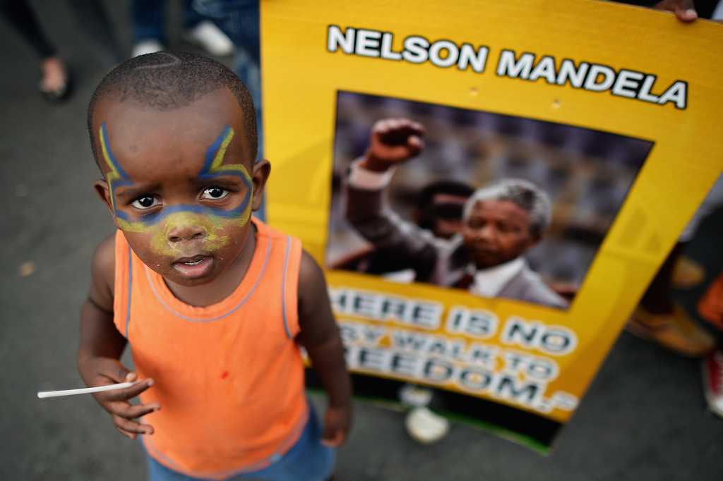 . A child stands with ANC supporters who were singing and dancing to celebrate the life of Nelson Mandela outside his former home in Vilakazi Street, Soweto Township, on December 7, 2013 in Soweto, South Africa. . (Photo by Jeff J Mitchell/Gallo Images/Getty Images)