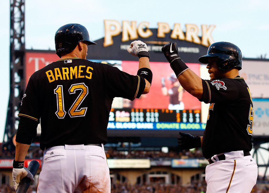 . Clint Barmes #12 and Russell Martin #55 of the Pittsburgh Pirates celebrate a run in the sixth inning against the St. Louis Cardinals during Game Three of the National League Division Series at PNC Park on October 6, 2013 in Pittsburgh, Pennsylvania.  (Photo by Jared Wickerham/Getty Images)