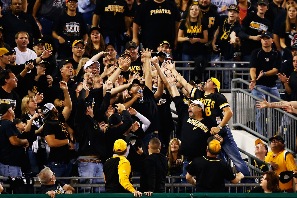 . PITTSBURGH, PA - OCTOBER 01:  Pittsburgh Pirates fans attempt to catch a second inning home run during their National League Wild Card game against the Cincinnati Reds at PNC Park on October 1, 2013 in Pittsburgh, Pennsylvania.  (Photo by Justin K. Aller/Getty Images)