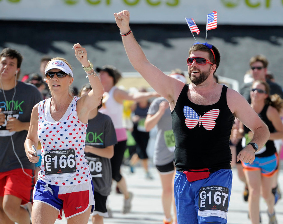 . Crossing the finish line dressed in the stars and stripes are Jana Stewart, from Canton, TX, left, and Kyle Tabor of Boulder. The 35th BolderBoulder 10k classic takes place on the streets of Boulder finishing at Folsom Field at the University of Colorado.  (Photo By Kathryn Scott Osler/The Denver Post)