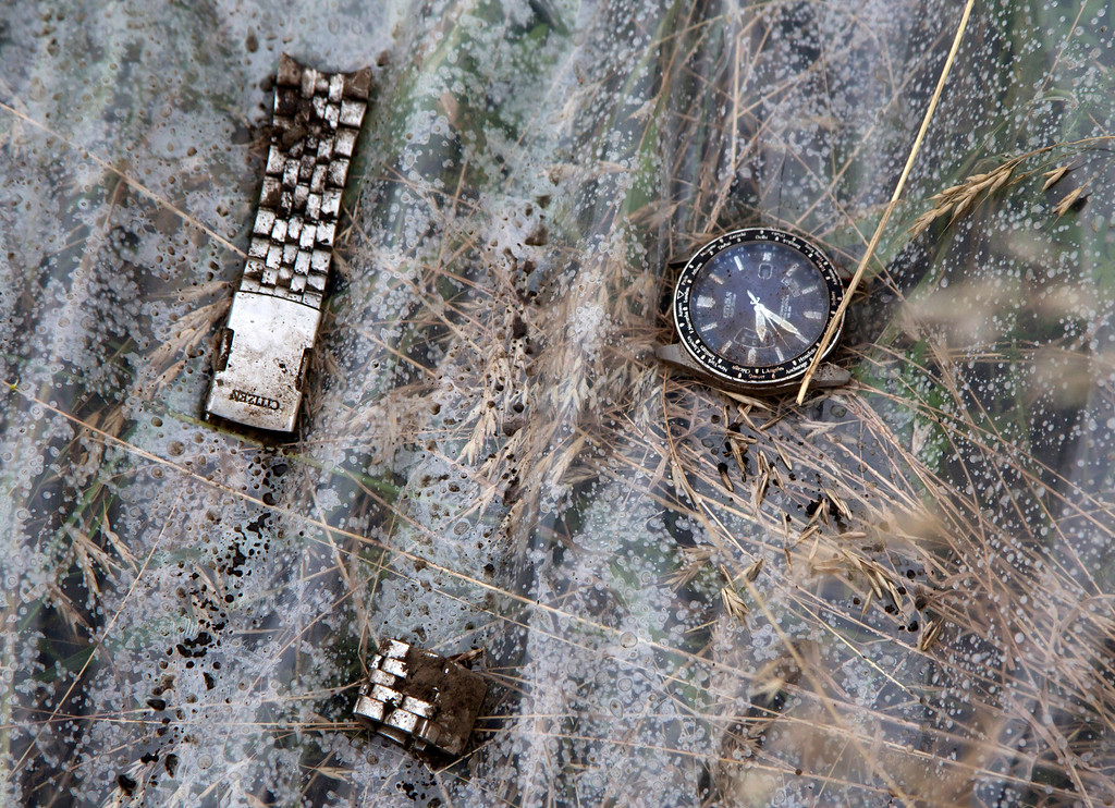 . A watch and a part of bracelet lie on a plastic cover at the site of a crashed Malaysia Airlines passenger plane near the village of Rozsypne, Ukraine, eastern Ukraine Friday, July 18, 2014. Rescue workers, policemen and even off-duty coal miners were combing a sprawling area in eastern Ukraine near the Russian border where the Malaysian plane ended up in burning pieces Thursday, killing all 298 aboard. (AP Photo/Dmitry Lovetsky)