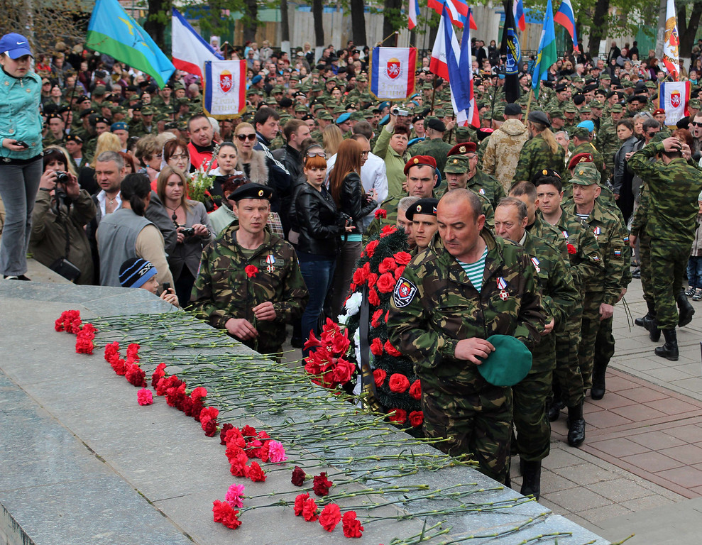 . Members of pro-Russian self defense forces lay flowers at a World War II memorial in Simferopol on April 13, 2014, during in the celebration of the 70th anniversary of the peninsula\'s capital Simferopol liberation from Nazi Germany troops in 1944. Crimea\'s largely Russian-speaking residents voted in March to become part of Russia, in a hastily organised referendum held as Russian troops patrolled the region.  AFP PHOTO/ YURIY LASHOV