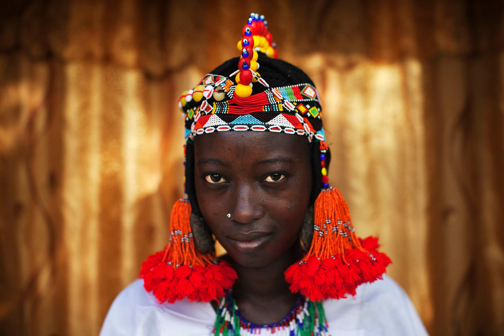 . Balkissa Maiga, 17, wears a traditional Songhai headdress made by artisan Hally Bara in Gao, Mali, March 6, 2013. Radical Islamist group MUJAO placed limitations on the wearing of traditional women\'s headdresses during their nine-month reign in Gao, which ended in January with the arrival of French and Malian troops. The headdresses, made of beads, gemstones, fabric and fake hair and traditionally worn by elites for special occasions, were criticised by MUJAO who said they were not Islamic enough. Issues surrounding the treatment of women are receiving special attention on March 8, which marks International Womenís Day. Picture taken March 6, 2013. REUTERS/Joe Penney