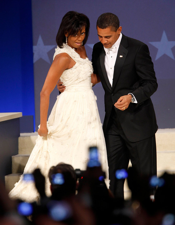 . President Barack Obama looks as first lady Michelle Obama straightens out her gown during their dance at the Western Inaugural Ball in Washington, Tuesday, Jan. 20, 2009. (AP Photo/Lawrence Jackson)