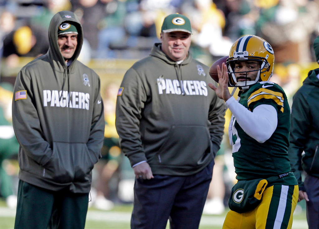 . Green Bay Packers head coach Mike McCarthy and Aaron Rodgers watch as quarterback Seneca Wallace warms up before an NFL football game against the Philadelphia Eagles Sunday, Nov. 10, 2013, in Green Bay, Wis. (AP Photo/Mike Roemer)