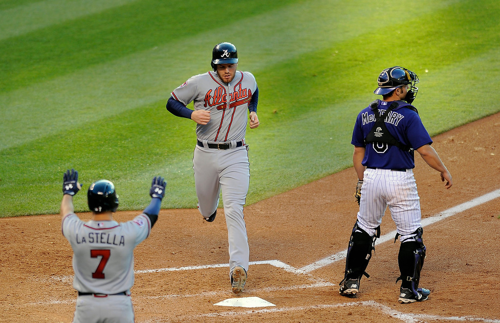 . Atlanta Braves Tommy La Stella, left. congratulates Freddie Freeman, center, as he crosses home plate on an RBI single by Chris Johnson as Colorado Rockies catcher Michael McKenry, right, waits for the throw in the fourth inning of a baseball game on Monday, June 9, 2014, in Denver. (AP Photo/Chris Schneider)