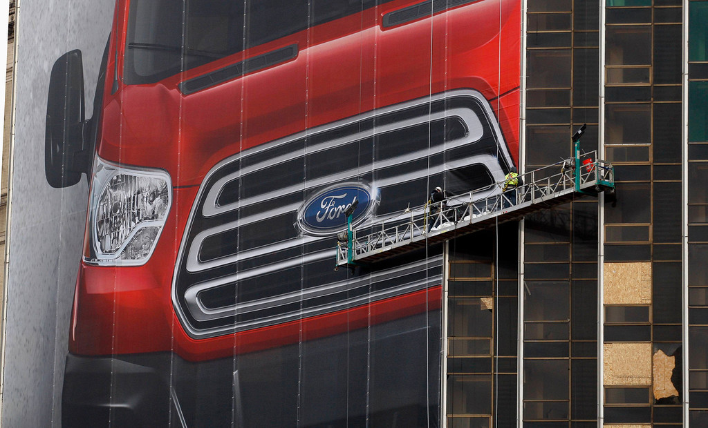 . Workers hang a Ford Motor banner on the side of a building across from Cobo Center in advance of the media preview of the North American International Auto show in Detroit, Michigan January 11, 2013.    REUTERS/Rebecca Cook
