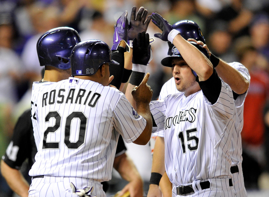 . Colorado Rockies\' Jordan Pacheco (15) is greeted at home plate by Wilin Rosario (20), Carlos Gonzalez (5) and DJ LeMathieu after hitting a grand slam off San Francisco Giants starting pitcher Madison Bumgarner during the fifth inning of a baseball game on Friday, May 17, 2013, in Denver. (AP Photo/Jack Dempsey)