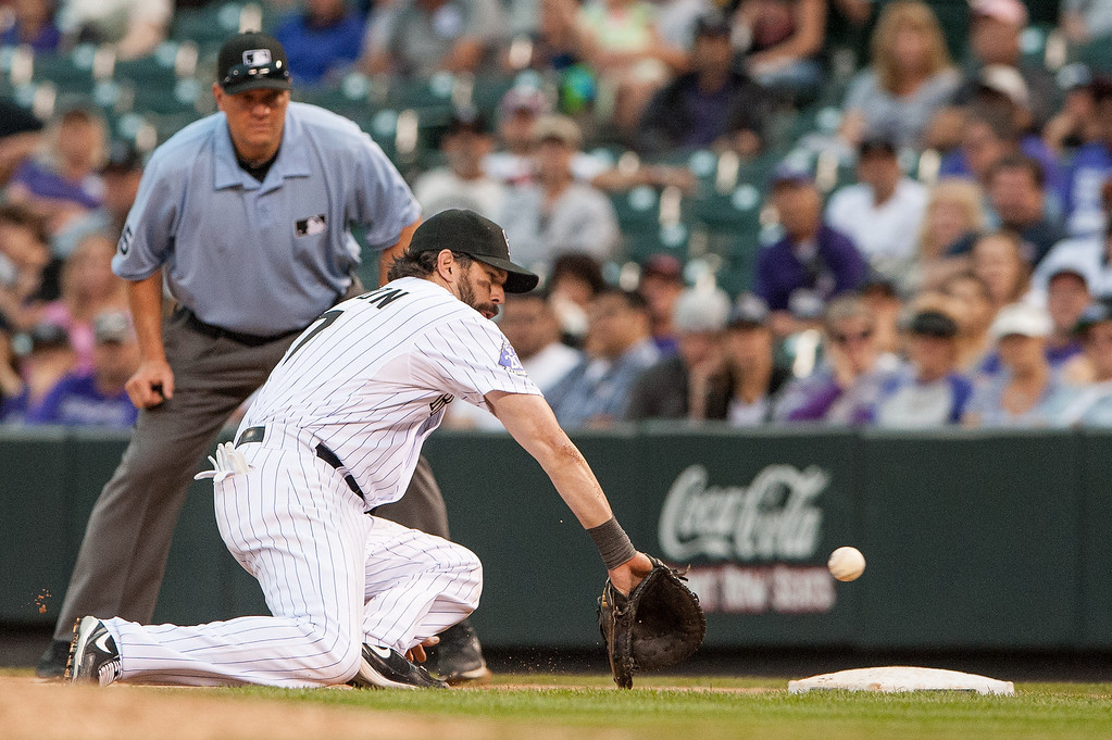 . Todd Helton #17 of the Colorado Rockies makes an attempt to field a ball down the line in the ninth inning of a game against the Arizona Diamondbacks at Coors Field on September 22, 2013 in Denver, Colorado.  (Photo by Dustin Bradford/Getty Images)