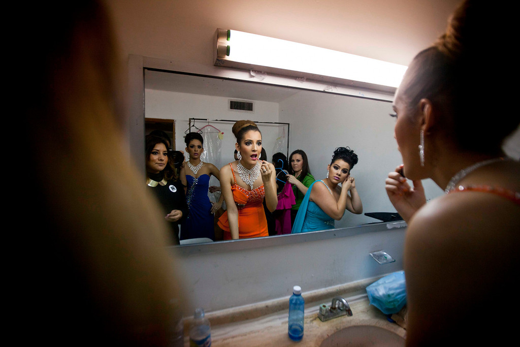 ". In this Jan. 26, 2013 photo, Donaji Lopez, 17, left in blue, Mayra Baez, 18, center, and Alejandra Angulo, 19, right, use the mirror backstage as they compete in the beauty pageant ""Guamuchil Carnival Queen 2013\"" in Guamuchil, Sinaloa state, Mexico. The farming town of 60,000 in the state of Sinaloa, despite its unpaved roads, is full of big mansions hidden behind high walls and iron doors decorated with ornate mirrors and life-size statues of angels.  The town has produced at least a Miss Mexico and more recently prides itself in saying the runner up to Miss World 2009 is a native. (AP Photo/Eduardo Verdugo)"