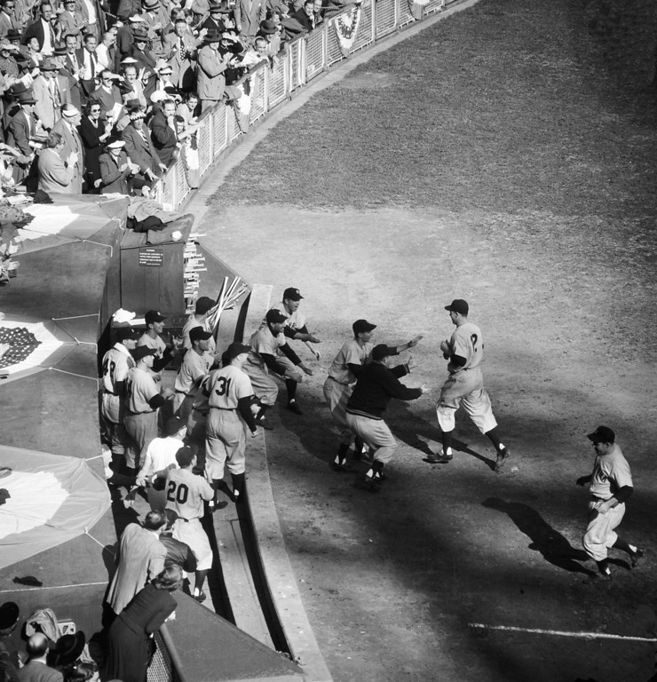 . New York Yankees\' second baseman Gil McDougald, right, is welcomed by teammates as they pour from the dugout after Gil\'s third inning grand slam homer in the fifth game of the World Series against the New York Giants at New York\'s Polo Grounds, Oct. 9, 1951.  The Yanks went on to win, 13-1.  (AP Photo)