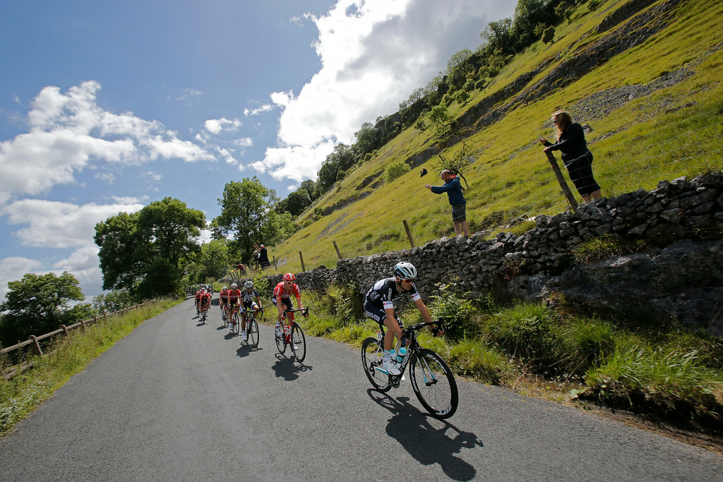 . The pack speeds down the rolling hills of Yorkshire during the first stage of the Tour de France cycling race over 190.5 kilometers (118.4 miles) with start in Leeds and finish in Harrogate, England, Saturday, July 5, 2014. (AP Photo/Christophe Ena)