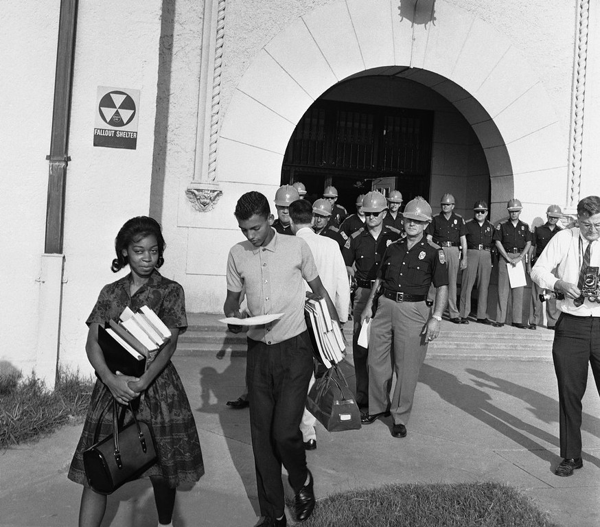 . With Alabama State Troopers blocking the main entrance to Murphy High School, students Dorothy Bridget Davis, 16, and Henry Hobdy, 17, arms loaded with school books, turn away from school, Sept. 9, 1963 in Mobile, Alabama. Hobdy is reading his copy of an executive order from Gov. George Wallace stopping the pair from attending classes. Murphy High is Alabama\'s largest high school with 3,300 students. (AP Photo/Fred Noel)