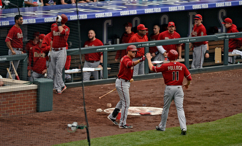 . DENVER, CO. - APRIL 21:  Martin Prado (14) of the Arizona Diamondbacks high fives A.J. Pollock (11) after scoring the game wining run on a Sacrifice fly to center fielder Eric Young Jr. (1) of the Colorado Rockies in the ninth inning April 21, 2013 at Coors Field. (Photo By John Leyba/The Denver Post)