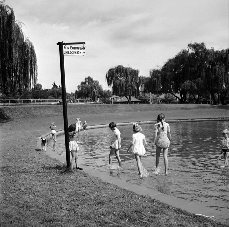 . circa 1956:  White children paddling in a pond marked by a sign reading \'For European Children Only\'.  (Photo by Three Lions/Getty Images)