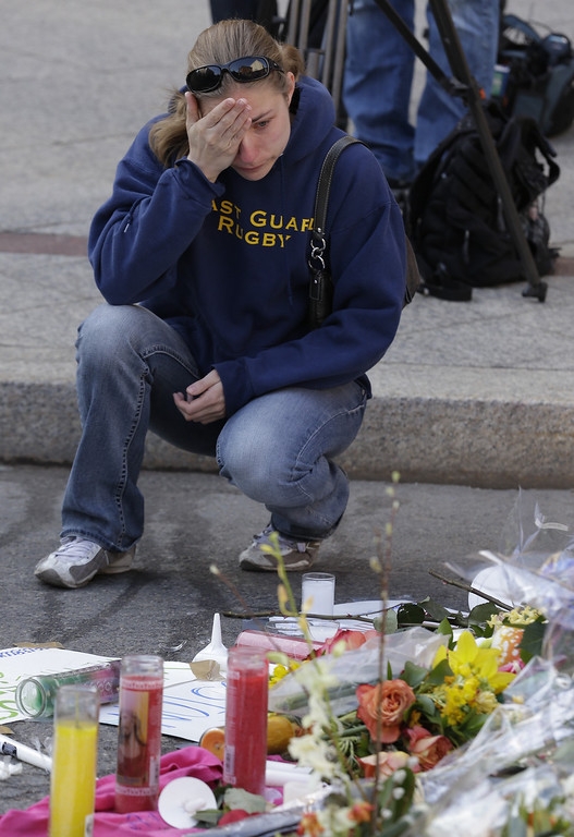. Jillian Blenis, 30, of Boston, reacts while stopping at a makeshift memorial, Wednesday, April 17, 2013, in Boston. The city continues to cope following Monday\'s explosions near the finish line of the Boston Marathon. (AP Photo/Julio Cortez)