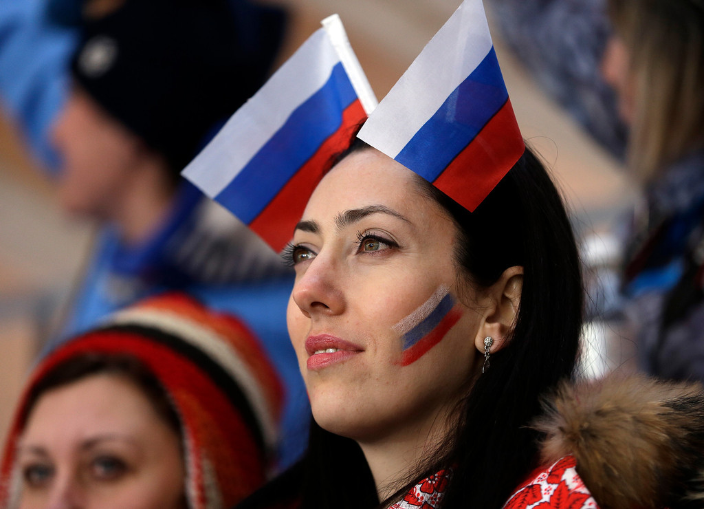 . A fan waits for the start of the men\'s singles luge final at the 2014 Winter Olympics, Sunday, Feb. 9, 2014, in Krasnaya Polyana, Russia. (AP Photo/Natacha Pisarenko)