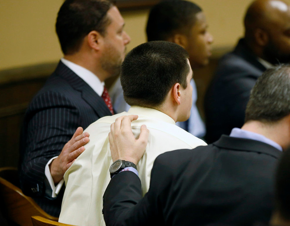 . Trent Mays is comforted by defense attorneys as he listens to the verdict in his trial at the juvenile court in Steubenville, Ohio March 17, 2013. Two high school football players from Ohio, Mays, 17, and Ma\'lik Richmond, 16, were found guilty of raping a 16-year-old girl at a party last summer while she was in a drunken stupor in a case that gained national exposure through social media. REUTERS/Keith Srakocic/Pool