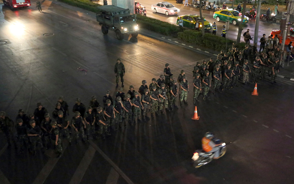 . A motorcyclist rides past Thai soldiers blocking the road to prevent activists and pro-government protesters from gathering to protest against the coup in downtown Bangkok, Thailand Friday, May 23, 2014. Ousted members of Thailand\'s former government turned themselves in to the country\'s new military junta Friday, as soldiers forcefully dispersed hundreds of anti-coup activists who defied a ban on large-scale gatherings to protest the army\'s seizure of power. (AP Photo/Apichart Weerawong)