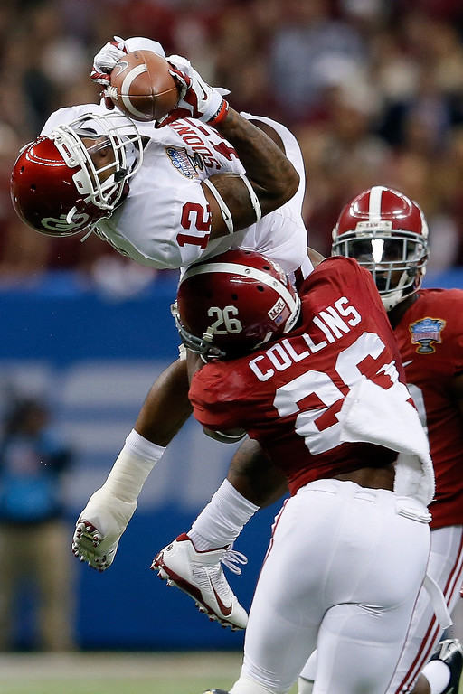 . NEW ORLEANS, LA - JANUARY 02:  Derrick Woods #12 of the Oklahoma Sooners makes a catch over Landon Collins #26 of the Alabama Crimson Tide during the Allstate Sugar Bowl at the Mercedes-Benz Superdome on January 2, 2014 in New Orleans, Louisiana.  (Photo by Kevin C. Cox/Getty Images)
