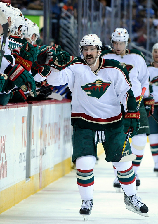 . Minnesota Wild right wing Cal Clutterbuck celebrates a goal against the Colorado Avalanche with teammates on the bench during the first period of an NHL hockey game on Saturday, March 16, 2013, in Denver. (AP Photo/Jack Dempsey)