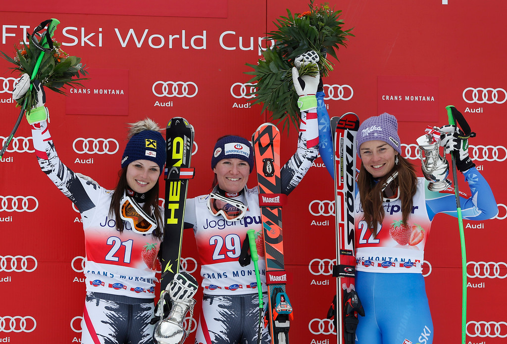 . Austria\'s Andrea Fischbacher, center, winner of an alpine ski, World Cup women\'s downhill, celebrates on the podium with second-placed Anna Fenninger, also from Austria, left, and third-placed Tina Maze, from Slovenia, in Crans Montana, Switzerland, Sunday, March 2, 2014. (AP Photo/Marco Trovati)