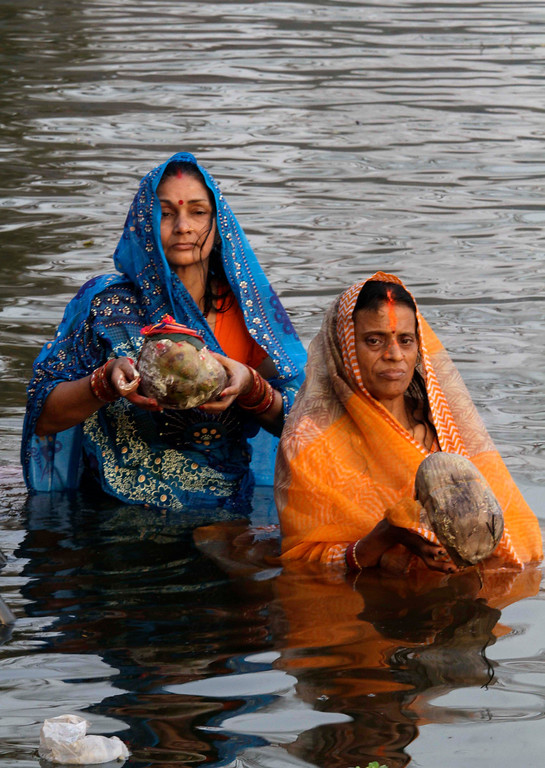 . Hindu women devotees perform rituals during the Chhath Puja festival at a lake in Kolkata, India, Friday, Nov. 8, 2013.   (AP Photo/Bikas Das)