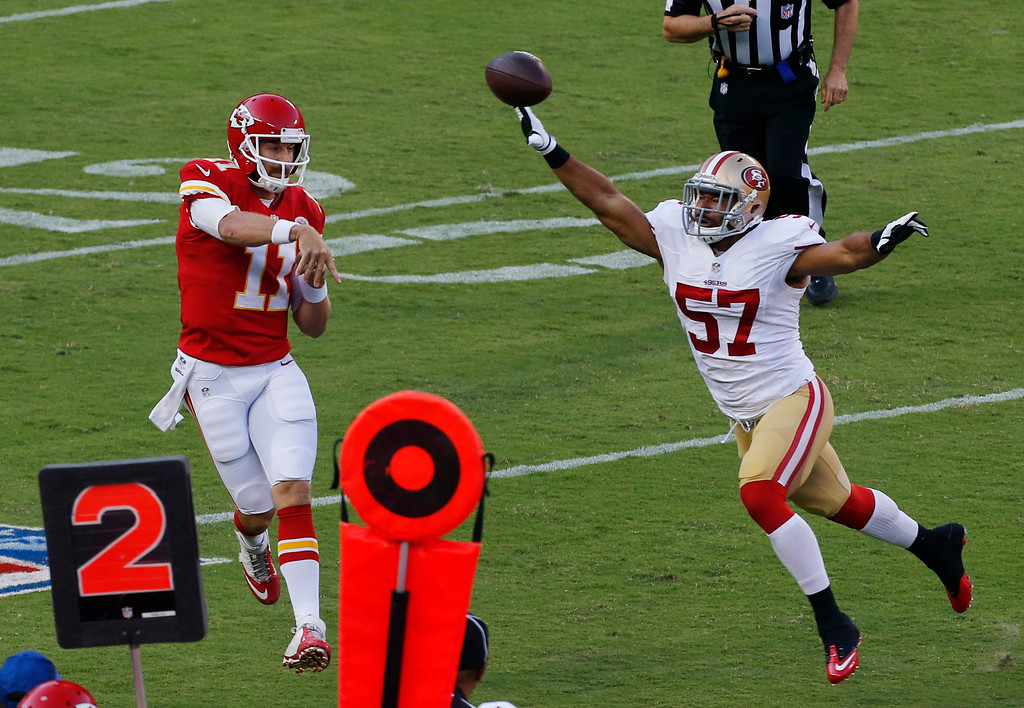 . Kansas City Chiefs quarterback Alex Smith (11) passes over San Francisco 49ers linebacker Michael Wilhoite (57) during the first half of an preseason NFL football game at Arrowhead Stadium in Kansas City, Mo., Friday, Aug. 16, 2013. (AP Photo/Orlin Wagner)