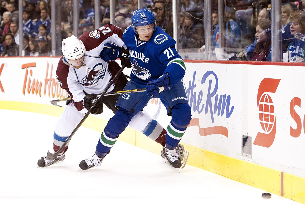 . Marc-Andre Cliche #24 of the Colorado Avalanche and Zac Dalpe #21 of the Vancouver Canucks battle for the loose puck during the first period in NHL action on December 08, 2013 at Rogers Arena in Vancouver, British Columbia, Canada.  (Photo by Rich Lam/Getty Images)