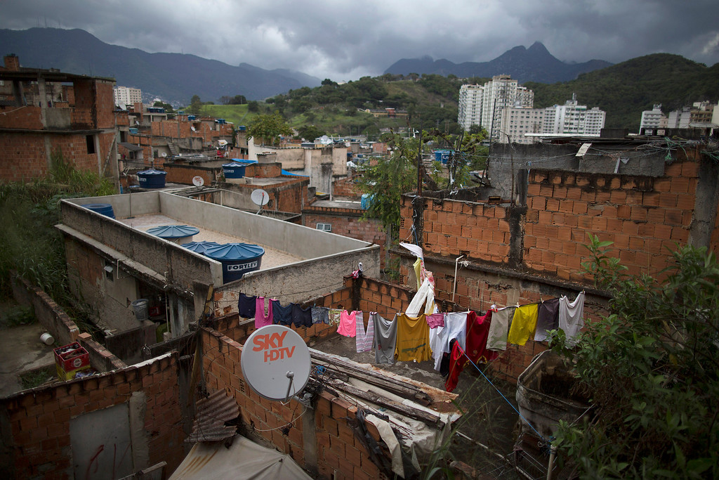 . In this Monday, June 2, 2014 photo, clothes hang to dry on the roof of a home in the Mangueira slum of Rio de Janeiro, Brazil. Less than half a kilometer separates the sprawling slum from the fabled Maracana stadium, where seven World Cup matches will be played, including the July 13 final. (AP Photo/Leo Correa)