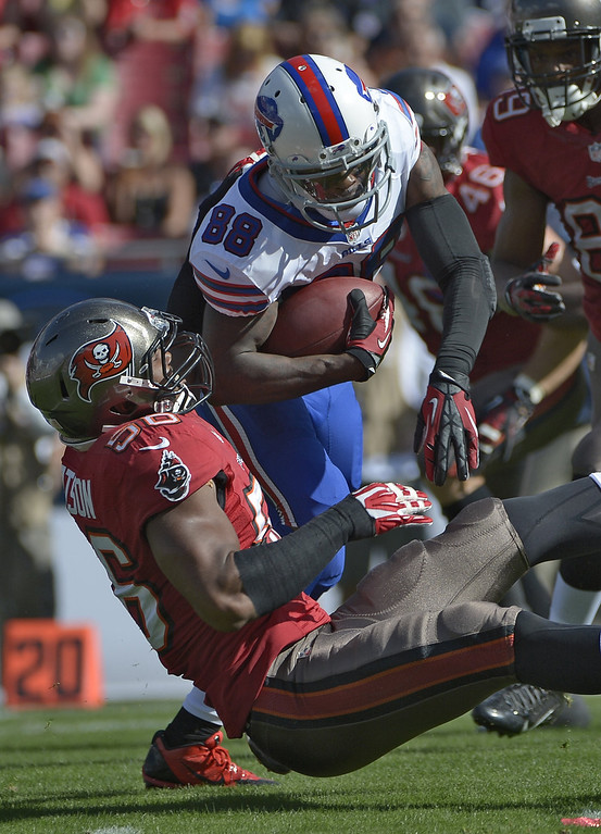 . Buffalo Bills wide receiver Marquise Goodwin (88) is grabbed by Tampa Bay Buccaneers linebacker Dekoda Watson (56) during the first quarter of an NFL football game on Sunday, Dec. 8, 2013, in Tampa, Fla. (AP Photo/Phelan M. Ebenhack)