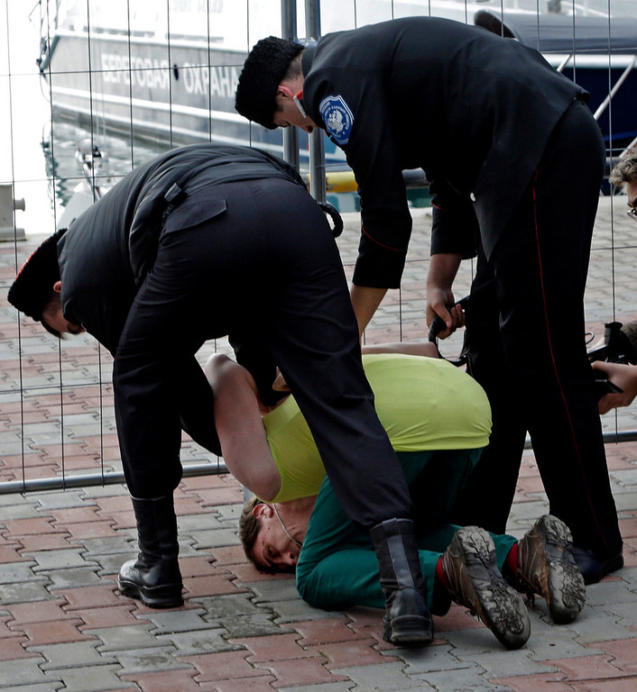 . A member of the punk group Pussy Riot is restrained by Cossack militia after the group tried to perform in Sochi, Russia, on Wednesday, Feb. 19, 2014. The group had gathered in a downtown Sochi restaurant, about 30km (21miles) from where the Winter Olympics are being held. They left the restaurant wearing bright dresses and ski masks and had only been performing for a few seconds when they were set upon by Cossacks. (AP Photo/Morry Gash)