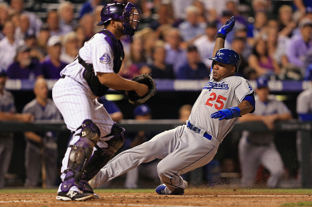 . Carl Crawford #25 of the Los Angeles Dodgers slides home to score behind catcher Wilin Rosario #20 of the Colorado Rockies on a sacrifice fly by Adrian Gonzalez #23 of the Los Angeles Dodgers to give the Dodgers a 4-0 lead in the fifth inning at Coors Field on September 3, 2013 in Denver, Colorado.  (Photo by Doug Pensinger/Getty Images)