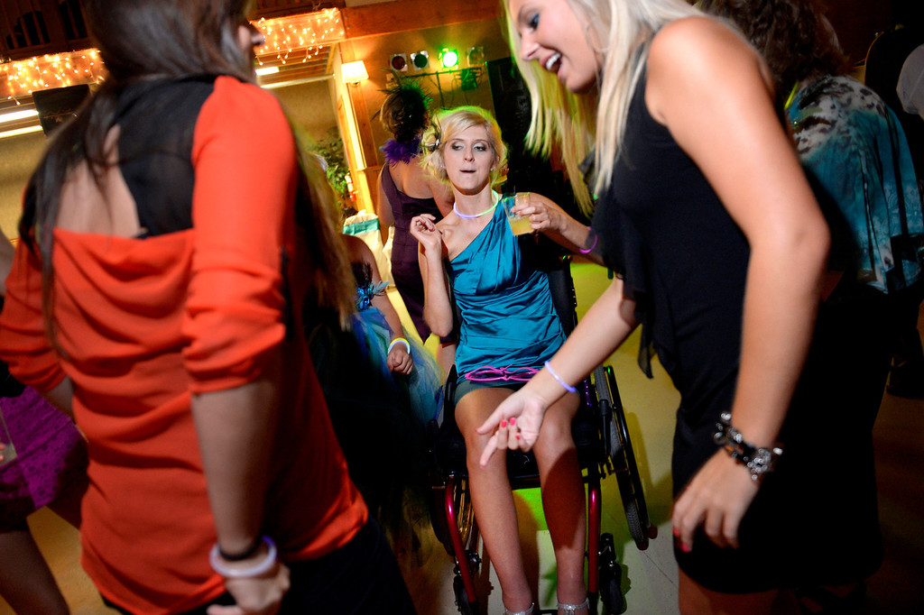 . Mackenzie cuts loose after a big moment at her sister Brittanie�s wedding, where her goal was to walk down the aisle under her own power. With some help, she used her own legs. Karen Gorden was relieved: �She tried to walk across the stage at graduation and that was a flop. She felt like she let everybody down. So this had some pressure on it.� (Photo By Craig F. Walker / The Denver Post)