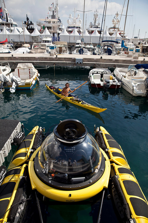 . A kayaker paddles past a C-Quester 3 submarine, manufactured by U-Boat Worx, as it sits moored during the Monaco Yacht Show (MYS) in the harbor in Monaco, France, on Wednesday, Sept. 25, 2013. Photographer: Balint Porneczi/Bloomberg