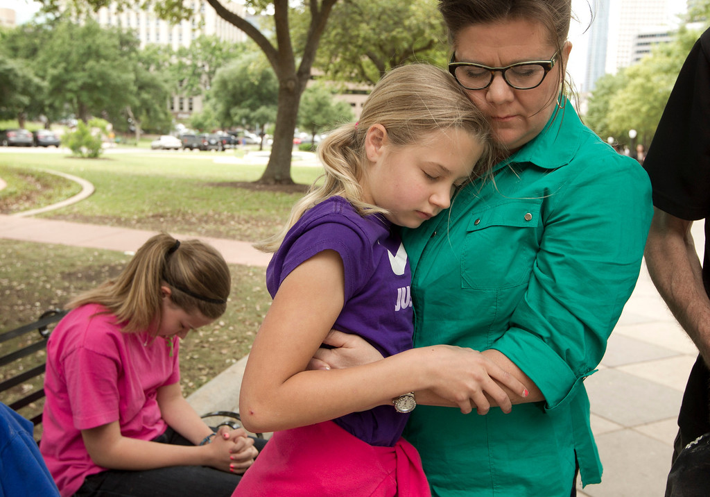 . Tonya Stevens and her daughters Jensen, left, 12 and Kristin, middle, 11,  pray during the One Voice United in Prayer event at the Capitol in Austin, Texas, on Thursday May 1, 2014.  About 100 people gathered at the Capitol on the 63rd Annual National Day of Prayer to sing praise songs and pray for the church, families, the military, education, the government, business and the media.    (AP Photo/Austin American-Statesman, Jay Janner)