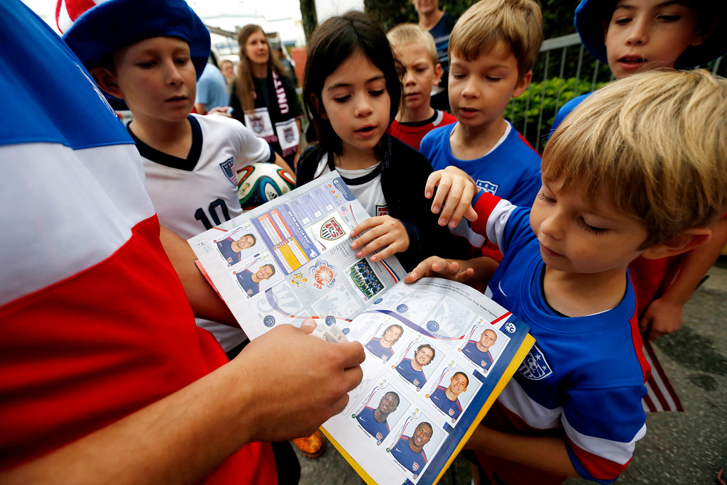 . Flavio Aquino, of San Diego, holds up a sticker book with portraits of the United States men\'s soccer team players as children gather around outside of the Sao Paulo FC training center where the U.S. is holding its training in Sao Paulo, Brazil, Wednesday, June 11, 2014. The U.S. will play in group G of the 2014 soccer World Cup. (AP Photo/Julio Cortez)