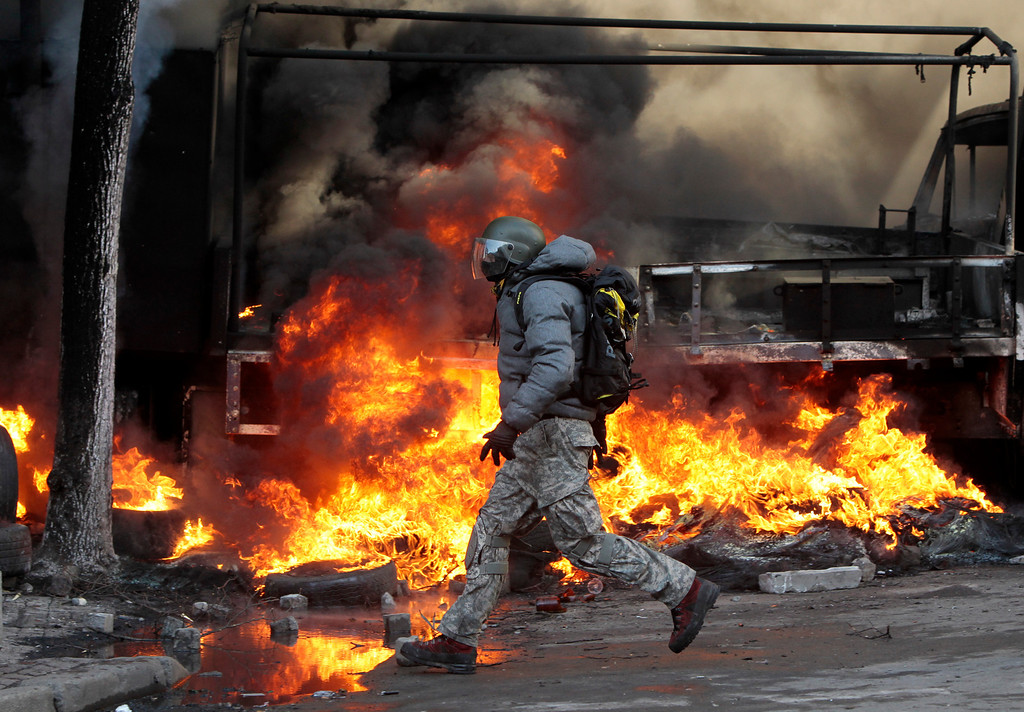 . An anti-government protester runs in front of a flaming barricade during clashes with riot police outside Ukraine\'s parliament in Kiev, Ukraine, Tuesday, Feb. 18, 2014. (AP Photo/Sergei Chuzavkov)