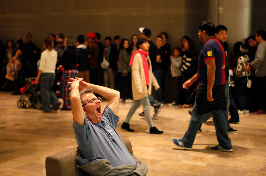 . A man, who declined to give his name, yawns and stretches out while waiting in a chair as hundreds wait in line to shop at Urban Outfitters in the Fashion Show mall in Las Vegas early in the morning of Friday, Nov. 29, 2013. Many of the stores in the mall opened at midnight for Black Friday. (AP Photo/Las Vegas Review-Journal, John Locher)