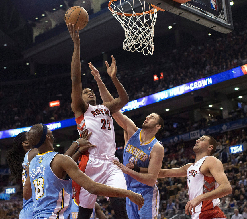 . Toronto Raptors\' Rudy Gay (22) scores on Denver Nuggets\' Corey Brewer, left, and Kosta Koufos as Raptors\' Jonas Valanciunas watches during the first half of an NBA basketball game in Toronto on Tuesday, Feb. 12, 2013. (AP Photo/The Canadian Press, Chris Young)