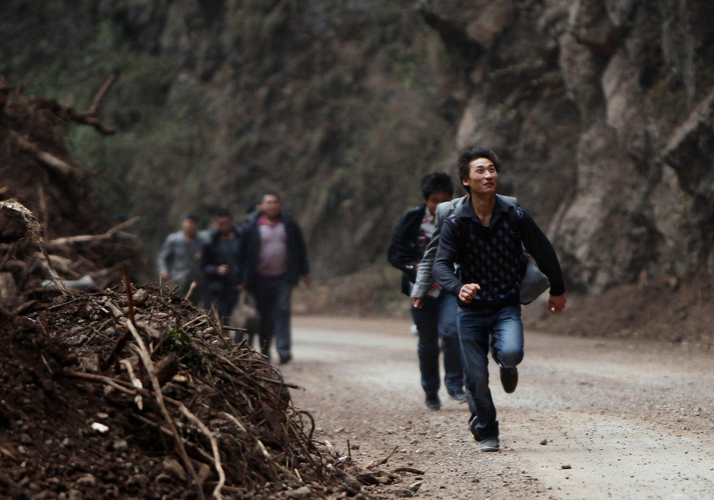 . A survivor looks up the mountainside as he runs past the debris of a landslide caused by Saturday\'s earthquake, on the side of a road to Lingguan township, in Baoxing county in Ya\'an, Sichuan province April 22, 2013. Rescuers struggled to reach a remote, rural corner of southwestern China on Sunday as the toll of the dead and missing from the country\'s worst earthquake in three years climbed to 208 with almost 1,000 serious injuries. The 6.6 magnitude quake struck in Lushan county, near the city of Ya\'an in the southwestern province of Sichuan, close to where a devastating 7.9 quake hit in May 2008, killing 70,000. REUTERS/Jason Lee