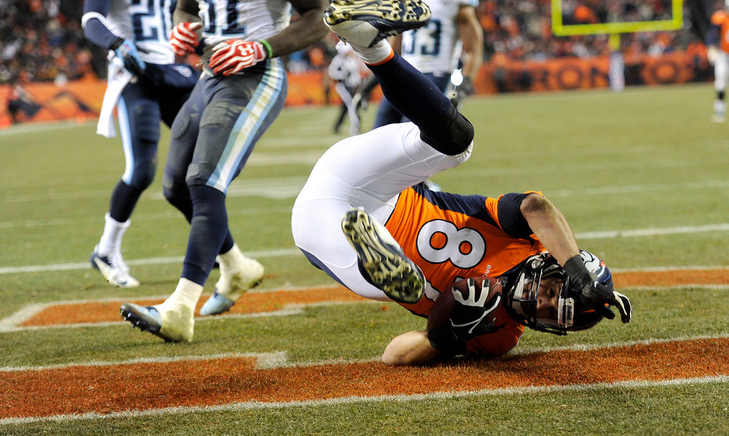 . DENVER, CO - DECEMBER 8: Denver Broncos wide receiver Eric Decker (87) rolls into the end zone for a fourth quarter touchdown.  The Broncos beat the Titans 51 -28. The Denver Broncos vs. the Tennessee Titans at Sports Authority Field at Mile High in Denver on December 8, 2013. (Photo by Joe Amon/The Denver Post)