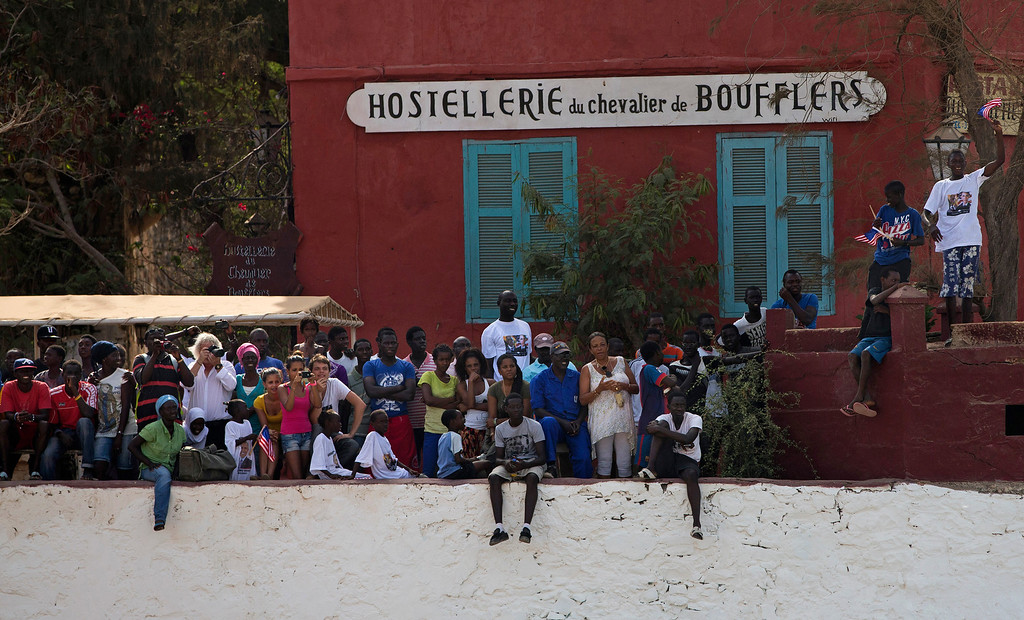 . A crowd watches as President Barack Obama takes a tour of Goree Island, Thursday, June 27, 2013, in Goree Island, Senegal. Goree Island is the site of the former slave house and embarkation point built by the Dutch in 1776, from which slaves were brought to the Americas. (AP Photo/Evan Vucci)
